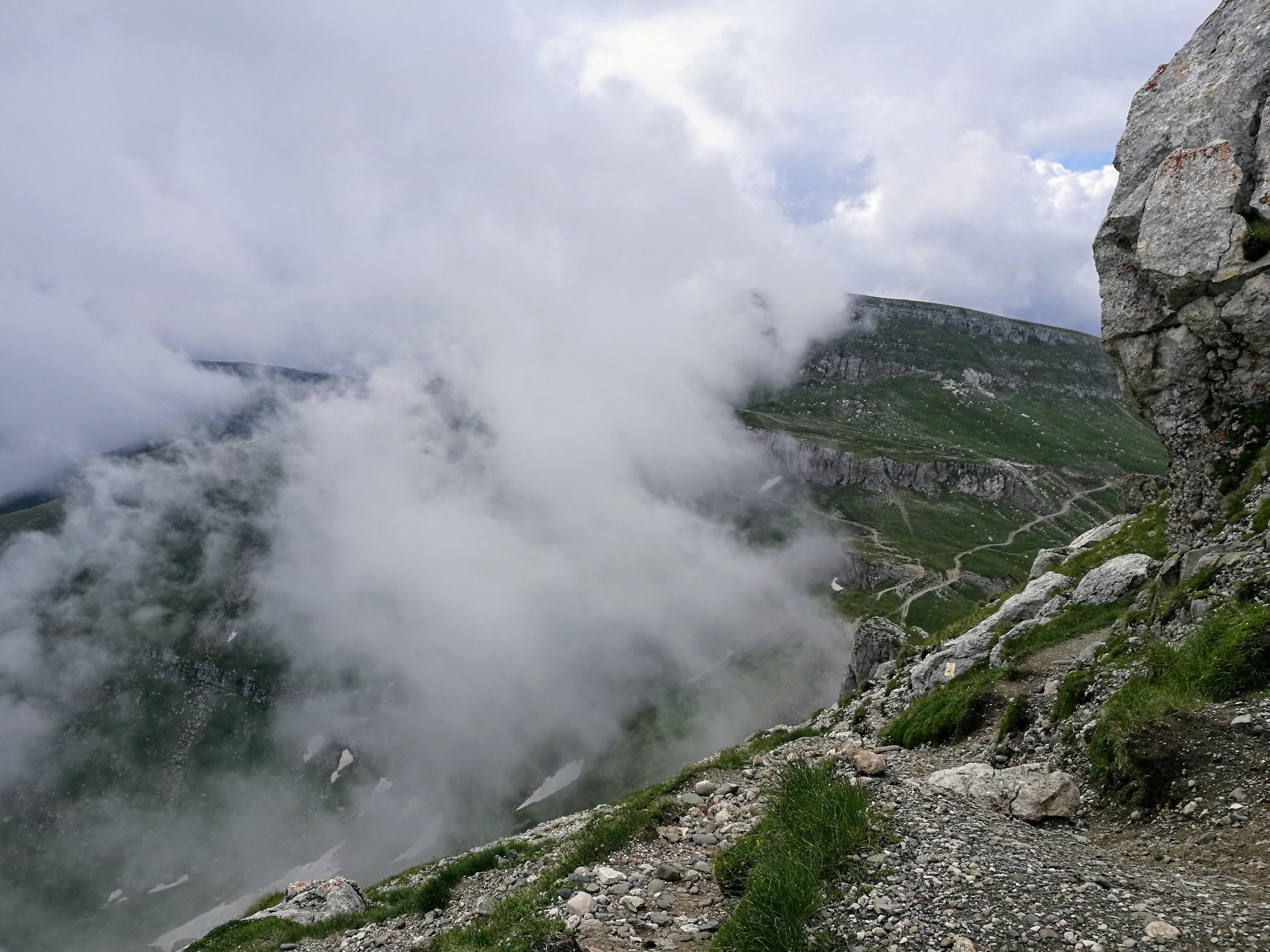 Coborarea de pe Bucsoiu spre Omu; cabana Omu e acoperita de nori